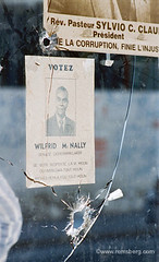 Political posters on store front with bullet holes through glass in Haiti. (Remsberg Photos) Tags: people glass danger town haiti power politics progress carribean safety posters tropical vote struggle bulletholes haitian thirdworld