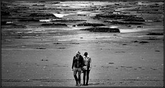 Walking on the moon (* RICHARD M (Over 5 million views)) Tags: street beach wet water mono togetherness blackwhite seaside sand mud candid space shoreline couples humour coastal together shore beaches holdinghands resorts puddles awayfromitall southport oblivious coasts merseyside wetsand sefton moonwalking inthezone farfromthemaddingcrowd holidayresorts besidetheseaside moonwalkers walkingonthemoon southportbeach onanotherplanet bowedheads pennyforem