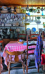 The living quarters in back of the store. (GeryLee) Tags: kitchen livedin pots pans kitchenchair blueshirt table tablecloth redandwhitetablecloth redandwhite crowded sidelight backlight