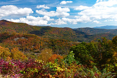 Multicolored Mountains (FagerstromFotos) Tags: autumn fall fallcolor outdoors nature clouds mountains blueridgemountains blueridgeparkway tanbarkridgeoverlook westernnorthcarolina northcarolina thecarolinas red orange green blue trees shrubbery plants