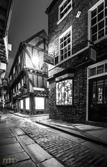 Little Shop of Light (M Hillier) Tags: shambles york medieval cobble cobbles cobbled street little shop jewellers jewellery timberframed building architecture blackandwhite black white mono monochrome monochromatic yorkshire north england greatbritain unitedkingdom portrait longexposure lamp narrow alley market dusk night dark autumn november ghost ghosts starburst bay window door road lane sign city nightscape blur people brick brickwork traditional tourists tourist shopkeeper shopkeepers closingtime
