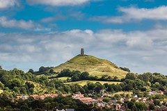 Tower on the Tor (Anthony Plancherel) Tags: england glastonbury landscape places somerset travel wirralhill travelphotography stmichaels canon tamron70300 canon70d landscapephotography landmarks hill hillside grass fields sky bluesky clouds greyclouds whiteclouds town houses residence uk unitedkingdom british greatbritain britain english outdoor wow