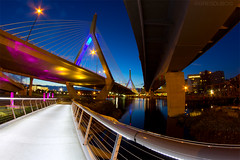 Break of Dawn from Under the Zakim Bridge, Curving Lines at North Point Park Cambridge (Greg DuBois Photography) Tags: park city longexposure morning bridge pink blue cambridge sky urban reflection water yellow boston architecture night composition canon river photography gold dawn movement highway cityscape nightlights view footbridge dam charlesriver perspective bridges dramatic wideangle lookingup lookup fisheye walkway bluehour 8mm cambridgema zakimbridge waterscape underbridge thecharles crossinglines samyang northpointpark charlesriverlocks leverettconnector samyang8mm gregdubois gregduboisphotography vision:night=0789