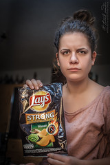 Serious wasabi (Neferkheperure) Tags: portrait woman girl look serious young indoor chips strong lays wasabi speedlite