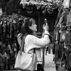 That one is mine (Go-tea 郭天) Tags: canon eos 100d 50mm street urban city qingdao china chinese asia asian people outside outdoor monochrome qingdaoshi shandongsheng chine cn bw bnw black white blackwhite blackandwhithe temple palace woman young phone religion religious mobile picture tree wishes pray praying photo take taking bag full loaded overloaded find lost selecting finding capturing capture social network hands addiction tao taoism