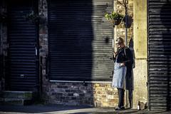 Sun seeker (tootdood) Tags: canon70d port street streetcandid candid manchester sun seeker mobile cell phone shade hanging basket flowers brick wall shutters