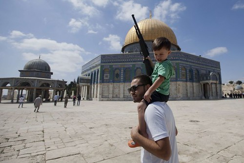 A Palestinian man carries on his shoulders a child holding a fake gun