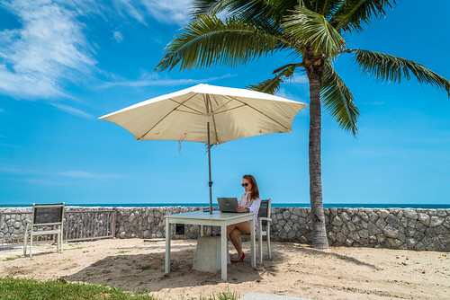 Woman use the laptop on the tropical beach in the shadow of umbrella