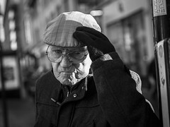 Hold On To Your Hat (Leanne Boulton) Tags: monochrome depthoffield people urban street candid portrait portraiture streetphotography candidstreetphotography candidportrait streetportrait eyecontact candideyecontact streetlife dutchangle man male elderly old face facial expression look emotion feeling eyes stare glare cap hat gesture stern angry tone texture detail bokeh natural outdoor sunlight light shade shadow city scene human life living humanity society culture canon 5d canoneos5dmarkiii 70mm ef2470mmf28liiusm character black white blackwhite bw mono blackandwhite glasgow scotland uk