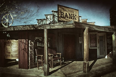 Pioneertown Bank (hbmike2000) Tags: california wood old windows usa west color building tree dusty architecture facade vintage buildings bench town wooden nikon doors bank scratches structure dirty dirt porch wetplate d200 dust scratched movieset saloon vignette hdr wagonwheel sanbernardino oldwest hss pioneertown dentistoffice saloondoors explored wagonwheelsaloon pioneertownbank sliderssunday hbmike2000 wepullemdentist