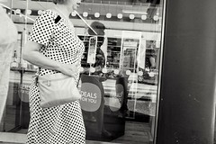 Slice of life (The Green Hornet ( Manchester)) Tags: manchester street photograpy monochrome life documentary woman walking sliced head dots polka dress shop window price tags vintage fujix100t