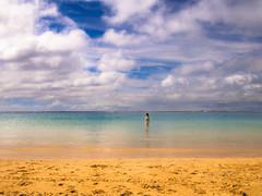 Wading Wahine in a Wild Hawaiian Sky (RobertCross1 (off and on)) Tags: 20mmf17panasonic alamoana em5 hi hawaii honolulu omd oahu olympus pacificocean beach bikini bluesky clouds female girl landscape makai ocean portrait sand seascape swimming swimsuit wading wahine water woman