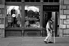 Stick Figure (Leanne Boulton) Tags: life street old city portrait people urban bw white man black monochrome shop canon walking scotland blackwhite sticks glasgow candid scene front human elderly disability blinkagain vision:text=0659 vision:outdoor=082