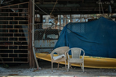old hangar by the sea (Tania's Tales) Tags: street city blue urban stilllife abandoned yellow barn outside boat chair furniture empty streetphotography armchair exploration            fotografiastradale taniastales