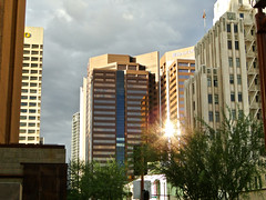 Sun spot on a cloudy day (phxdailyphotolady) Tags: arizona sun storm phoenix clouds buildings downtown glare highrise