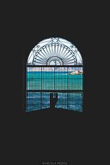 Through the gate (Nicola Pezzoli) Tags: favignana sicilia sicily island egadi summer sea water colors nature canon tourism gate florio tonnara stabilimento blue silhouette