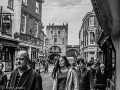 A street in York with Monk Bar in the distance. (steve.gombocz) Tags: urbanstreet blacknwhite greyscale monochrome streetscene blackwhite whiteblack bwstreetscenes bw bwstreet flickrstreet bwflickr blackwhitephotos blackwhitephotography blackwhitestreet bwstreetphotography streetlife street blackandwhite streetscenes streetphotographs bwphotographs streetphotography bwphotography streetbw noiretblanc schwarzundweiss negroyblanco zwartwit neroebianco sortoghvid mustavalkoinen svarthvitt svartoghvitt svartochvitt czarnyibiaty pretoebranco noirblanc schwarzweiss negroblanco nerobianco pretobranco olympuscamerausers olympus olympususers olympusbw olympusmzuiko25mmf18lens photosinblackandwhite flickrblackandwhitephotos olympusdigitalcamerausers micro43rdsuk olympuszuikodigitalclub olympuseurope olympusstreet bwpictures york yorkbw yorkmonochrome yorkscenes monkbar yorkmonkbar yorkphotographs yorkblackwhite flickraddict explorestreet out outandabout explorebw tuttiicoloridelnero streetphotos purestreet streetpictures