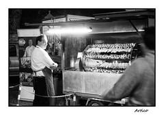 Skewered (Artico7) Tags: skewer skewered meat sausage sausages chicken festival rivignano fieraseisanti sagra man light cook cooking fluorescent street streetfood food bw blackandwhite blackwhite biancoenero fuji xe1 monochrome friuli italy
