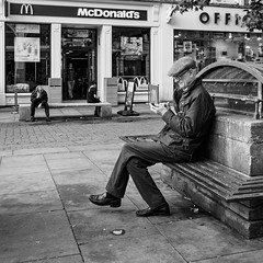 Manchester 046 (Peter.Bartlett) Tags: manchester square noiretblanc shopfront olympusomdem5 unitedkingdom bench people streetphotography urbanarte window cellphone sign peterbartlett man urban sitting candid uk m43 microfourthirds mobilephone bw texting macphuntonality blackandwhite shopwindow lunaphoto england gb