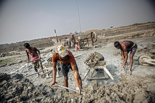Men piling mixture for brick onto a wheelbarrow, Khulna, Bangladesh. Photo by Felix Clay/Duckrabbit.