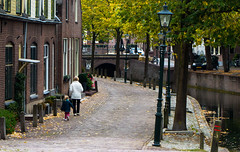 Following grandma through the old autumn streets . . (Eduard van Bergen) Tags: road vista morning time water land village sun light houses trees line perspective way clouds holland tulips shoes niederlande netherlands antje frau cheese blue green woman oiseau hamlet outdoor building architecture pays bas nieuwpoort alblasserwaard molenwaard lek rijn rhine harbor dikes wall stad town stadje vesting stronghold fortress canons kanonnen fort old vintage ancient yard tree plant window manor grandchild child family nanny granny grandma girl little city fortification