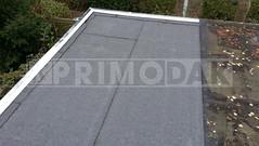 Dakdekker: Bij dit gemeenschappelijk plat dak de dakbedekking vervangen van een berging. Links het dak overlaagd met Uniegum 470 K24 met een waterdichte aanhechting op het oude dak van de buren rechts