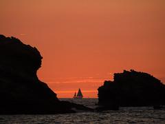 Orange Coloured Sky (DaveKav) Tags: sunset orange france silhouette boat rocks sailing olympus 64 biarritz paysbasque e510