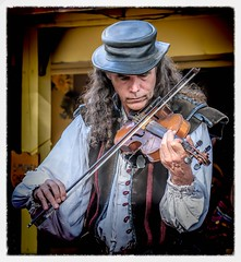 The Fiddler (Wes Iversen) Tags: clichesaturday hcs holly michigan michiganrenaissancefestival nikkor18300mm fiddles hats men music musicalinstruments people portraits violins musicians