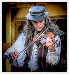 The Fiddler (Wes Iversen) Tags: clichesaturday hcs holly michigan michiganrenaissancefestival nikkor18300mm fiddles hats men music musicalinstruments people portraits violins musicians