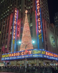 Radio City Music Hall, Rockefeller Center, New York City (jag9889) Tags: 20161201 jag9889 neon building manhattan rockefellercenter landmark newyork outdoor 2016 theatre light radiocitymusichall barriers sixthavenue text midtown people newyorkcity crowd facade rockettes christmastree usa nightphotography metal architecture house longexposure ny nyc night nightscene performance theater unitedstates unitedstatesofamerica us