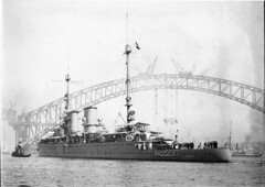 """The """"Java"""", a warship of the Dutch East Indies, berthing with the Sydney Harbour Bridge as a background, ca. 1930 / Ted Hood"""