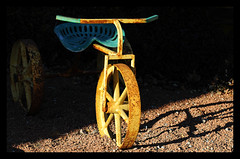 Farmer's Tricycle (thepoocher7) Tags: outdoors weathered rusty rust tractorseat farmers tricycle ornament trike yellowpaint wornpaint rustywheels green yellow art lawnornament light shadow spokes wheels gravel iron