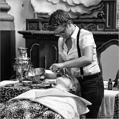 """You'd better sit still while you're being shaved"" (Dutch saying) (John Riper) Tags: johnriper street photography straatfotografie schiedam square bw black white zwartwit mono monochrome netherlands candid john riper canon 6d 24105 l cultural event jenever genever gin jeneverfestival gincity barber shop woman lady man shaving cream"