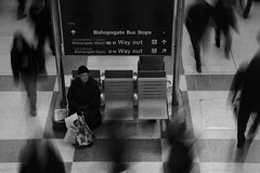 DSC00303 a still old lady in Liverpool Street Station, Londond (roger_thelwell) Tags: life street city uk winter portrait england people urban bw white black streets cold reflection brick london monochrome face hat mobile train hair walking real photography mono chat phone faces natural photos britain candid great hats cell railway photographic photographs lane conversation talking spitalfields speak speaking commuters londond {vision}:{text}=0679 astilloldladyinliverpoolstreetstation