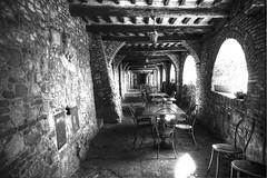 sotto le mura medioevali. (Enzo Ghignoni) Tags: mura travi archi tavoli sedie pietre luce italia bianco e nero