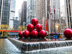 Great Balls of Fire (Mildred Alpern) Tags: ornaments splashingwater buildings outdoor nyc red radiocitymusichall christmas decorations