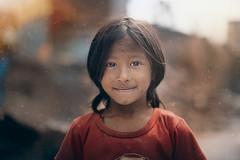 Little girl among the debris after earthquake (Fabien Lasserre -) Tags: rouge smile color debris dust spark sparks dusty face girl beauty nepal kathmandu katmandou earthquake tremblementdeterre streetportrait bokeh slum