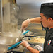 A cook mans woks out some beef noodles at Flashpoint, one of the new choices for dining at On The Oval.