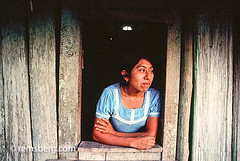 Latin American woman looking out of window in a traditional home in Belize. (Remsberg Photos) Tags: wood woman home window solitude sill belize happiness relaxation tradional centralamerica latinamerican bluedress conent
