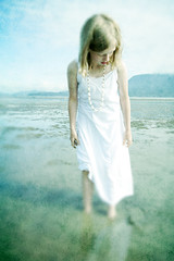 Young girl standing at the edge of the sea wearing a sundress and sea shell necklace (Marlene's photography) Tags: sea summer shells white mountains texture water beautiful childhood vertical youth fun outside outdoors freedom alone child calm simplicity dreamy simple solitary pure tranquil carefree atmospheric enchanted sundress oneperson textured younggirl purity enchanting mutedcolours