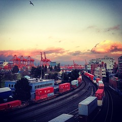 January sunset makes pink clouds... (HappyBarbers) Tags: instagramapp square squareformat iphoneography uploaded:by=instagram xproii gastown vancouver sunset glow trains traintracks cranes mountains sky clouds eastvan vancity january winter afternoon view portofvancouver insidevancouver