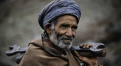 Steve McCurry (grantmckelvey) Tags: 1983 pakistan landi kotal landikotal horizontal portrait outdoors outside exterior adult man old elderly carry carrying hold holding wrench hammer tool tools robe wrap shawl coat turban beard mustache wrinkle wrinkles wrinkled skin shoulder blue gray brown 0046111 pakistan10006nf iconicphotographs portraits app landekotal