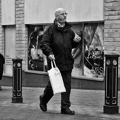 Pastie Walk (Peter.Bartlett) Tags: street city people urban blackandwhite man monochrome pen walking mono blackwhite unitedkingdom eating candid yorkshire streetphotography olympus nik olympuspen westyorkshire huddersfield blackdiamond ep3 m43 kirklees blackwhitephotos urbanarte streetphotographyurban fragmentsoftime niksilverefex microfourthirds peterbartlett olympuspenep3