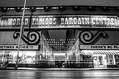 World Famous Bargain Centre (Matt M S) Tags: street city longexposure light urban bw white signs toronto ontario canada black streets reflection classic wet car rain sign architecture night vintage reflections dark flow lights store discount community stream long exposure downtown village traffic metro trails icon canadian architectural retro honest trail rainy signage to eds gta iconic bathurst honesteds metropolitan bloor streaming bargain annex the blogto mirvish torontoist cartrailsatnight