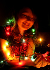 Anna with lights (Ginni B) Tags: christmas blue light red portrait anna green girl beautiful smile yellow bulb night hair lights wire traditional daughter smiles curls cable here illuminated bulbs were curl lovely tradition wah nearly nightportrait twelfth werehere hpad hereios