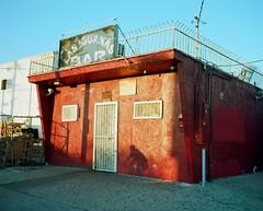 Orange bar, cyclist (ADMurr) Tags: la hawthorne southla orange bar shadow bike cyclist blue evening mamiya 7 6x7 kodak ektar 80mm