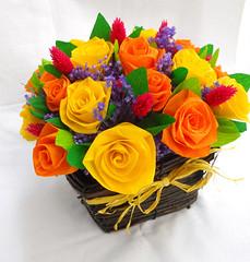composizione floreale giallo arancione viola in vaso di legno