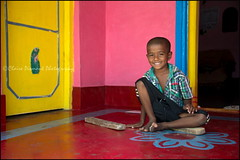 Innocence. Somnathpur (Claire Pismont) Tags: asia asie inde india karnataka boy kid clairepismont pismont portrait pink yellow colorful couleur color colour child rangoli smile travel travelphotography documentory somnathpur voyage viajar village