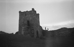 Kick the Can Castle (Joybot) Tags: 2003 old people blackandwhite bw blur tower castle history film silhouette wall wales 35mm grey climb blurry ancient shadows hill blurred climbing historical walls flou battlements