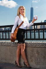Low Angle View of a Woman Standing While Holding a cup of Coffee During the Morning Commute with Lower Manhattan Skyline in the Backround (George Oze) Tags: city newyorkcity urban woman usa sexy smiling vertical river walking outdoors happy newjersey model jerseycity slim riverside manhattan blueeyes unitedstatesofamerica scenic lifestyle skirt trendy blonde attractive jersey northamerica commuter manhattanskyline hudsonriver daytime hip lookingdown youngwoman morningcommute beautifulpeople fit slender caucasian whiteshirt officeworker hudsoncounty toothysmile blackskirt energetic onewomanonly whiteblouse lookingatcamera pencilskirt americanwoman lowangleview caucasianethnicity whitecollarworker caucasianwoman fairskinned corporateattire holdingcup tonedbody facingcamera professionalwoman lowangleperspective professionallook modernlook fullbodylength 3035yearsold mid30yearsold tonedthighs